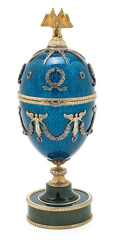Fabergé Easter Egg Silver, engraved and partially gilded with blue guilloché enamel, oval cabochon rubies, round and oval cabochon tourmalines, and rose cut diamonds; with nephrite jade pedestal. Egg topped by an Imperial double-headed Romanov eagle, and opens to reveal a gold and enameled elephant. Workmaster Henrik Immanuel Wigström. With original case in birch and silk and Imperial coat of arms.