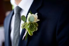 This green and ivory boutonniere stands out against the groom's navy blue suit.