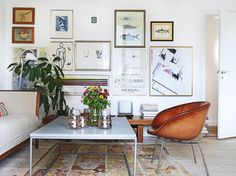 white walls, salon wall, kilim, worn-leather, canvas upholstery, book stacks, bright & light / LOVE THIS SPACE