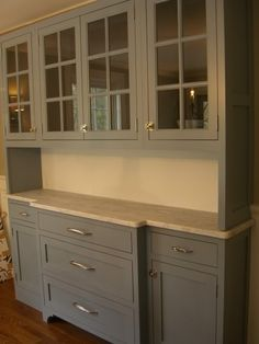 Gray painted built-in hutch w/ marble countertop. OR take the upper cabinets all the way down to counter. It is narrow and for housing dishes and glasses. Not food storage.