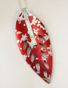 I made this in anodised aluminium which I'd printed and dyed.  It was saw-pierced and finished in sterling silver.