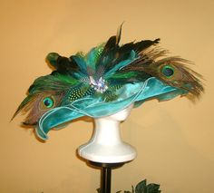 A inch Satin down brim Kentucky Derby Hat trimmed with a long, peacock eyes and swords, hand dyed guinea, schlappen, chinchilla and rooster. Derby Time, Derby Day, Blue Crayon, Victorian Hats, Spring Shorts, Kentucky Derby Hats, Crystal Brooch, Cute Hats, Party Hats