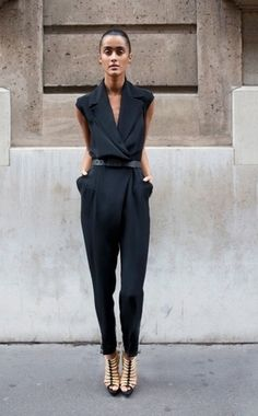 Sleeveless narrow black jumpsuit with deep plunge neckline, surplice bodice, belted defined waist, pockets at the hips and pegged trousers. Gold cage wedges. Oh yeah. Style Planet #black jumpsuit #elegant black jumpsuit #haute black jumpsuit #designer black jumpsuit