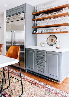 Okay, so this is actually the space space as the first image above... bonus points to the designer for finding not one but TWO of the most beautiful vintage runners EVER. It really isn't that hard to mix and match patterns in a small space - just stick to the same color palate! (source) #bluekitchen #interiordesign #leatherbarstool #leatherchair #openshelving #kitchendesign #kitchen