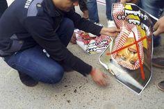 Een demonstrant probeert het portret van de Saudische kroonprins Mohammed bin Nayef in de brand te steken. Na de executie van de sjiitische geestelijke Nimr al-Nimr in Saudi-Arabië is in Irak op diverse plaatsen fel geprotesteerd. Irak is overwegend sjiitisch.