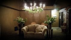 barn transformed by huge chandelier, love seat, and plants near the changing rooms.