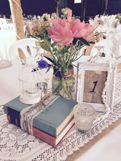 Burlap and lace mason jar wedding centrepiece - rustic wedding - vintage wedding styled by #mashedevents. Burlap table number frame, vintage books, birdcage, pearls