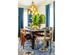 A patterned rug and rich curtains bring color to this dining room, while a potted tree lends a natural touch. Black and white chairs head the dining table, adding another stylish pattern to the mix, and a beautiful chandelier adds light and interest overhead.