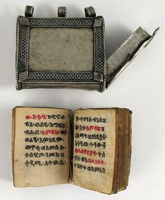 Beautiful old prayer amulet containing a tiny parchment Coptic bible written in Ge'ez and bound with a wooden cover. The Ge'ez or Ethiopic script possibly developed from the Sabaean/Minean script. The earliest known inscriptions in the Ge'ez script date to the 5th century BC. Ge'ez, the classical language of Ethiopia which is still used as a liturgical language by Ethiopian christians and the Beta Israel Jewish community of Ethiopia.