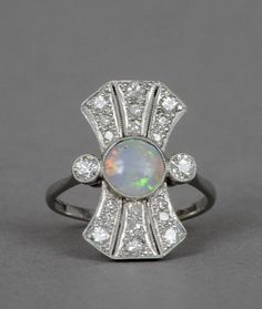 An Art Deco opal and diamond set 18 ct white gold and platinum ring, stamped 18 & PT --Generally in good condition, expected wear, size L.