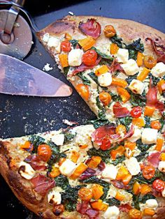 Wholewheat pizza with spinach, serrano ham, cherry tomatoes. feta cheese and orange bell pepper