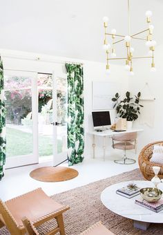 Live/work space with tropical printed curtains, a  seating area with a woven rug, and a desk in the corner