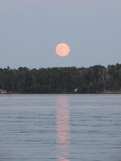 a lake with an orange moon