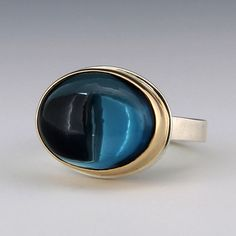 """London blue topaz is sought after for its deep vibrant color, and this Jamie Joseph ring features a beautiful speciman. The oval cabochon topaz is set in a 14k yellow gold bezel and sits on a sterling silver """"X"""" band. <br><br>Stone measures 1/2"""" x 3/4"""". <br><br>Size 5.75.<br><br><div><b>Special Sizing:</b></div><div>There is no charge for a first time sizing. </div><div>Delivery for a special sizing is 4 weeks.</div><div><br></div><div>Please contact us below for a special sizing…"""