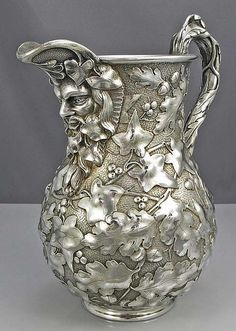 Jacobi sterling water pitcher with face and Ivy leaves.
