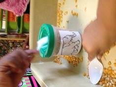 "Preschool fine motor practice- ""feeding"" animals using paint cups and popcorn kernels"