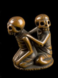 odditiesoflife: Netsuke in form of seated skeletons Skeletons often appear in netsuke. They are sometimes in quite comic poses. This tiny wooden netsuke is in the form of two seated skeletons. The one behind has his hands on the other's shoulders. The meaning of the imagery is uncertain. The netsuke was made in Japan. Netsuke are toggle-like ornaments. They hang objects such as medicine boxes or tobacco pouches from the sash of a kimono – a traditional form of Japanese dress. Netsuke carv...