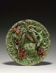 A PORTUGUESE MAJOLICA TROMPE L'OEIL CIRCULAR DISH  Circa 1880, impressed seal mark for Antonio Alves, Cunha, Caldas da Rainha  Moulded and applied with three frogs, two lizards before grassy hides and a snake, on a bed of mossy frit  13 in. (33 cm.) diameter Antique Pottery, Famous French, Table Scapes, Lizards, Forks, Earthenware, Spoons, Portuguese, Knives