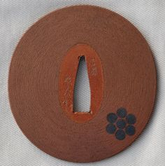 A fine ubu tsuba by Yoshioka Terutsugu, the seventh master of the Yoshioka Inabanosuke line. A lovely red copper tsuba with mon in shakudo honzogan, the surface finished in fine nanako. 7.52 cm x 7.12 cm x 3.8 mm. He was the adopted son of Kiyotsugu and became head of the family on December 26, 1774. Upon the death of Kiyotsugu in 1802, he became the seventh master. He was a retainer to the Tokugawa Bakufu, and received a stipend of 100 koku of rice. He died at the age of 89. $3,750