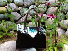 The Buckaroo Tote. This one has the diaper bag lining with large pockets to hold diapers and wipes, a sleeve to hold a bottle upright and a hook to hold keys safely inside. The turquoise suede initials are the little baby boy's. gowestdesigns.us