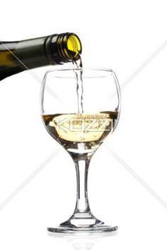 white wine being poured in glass - Close-up of white wine being poured in wine glass over white background