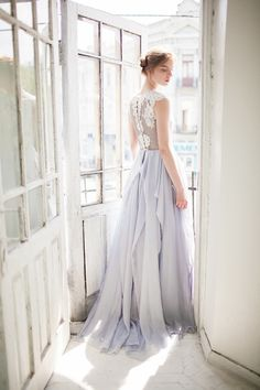 This periwinkle gown with an elaborate lace bodice and a skirt with delicate…