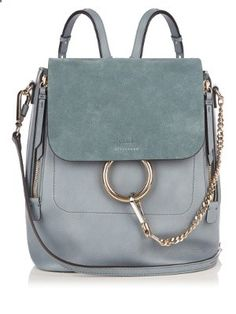 Arriving in a dreamy slate-blue shade, Chloés grained-leather Faye backpack will perfectly complete refined denim looks. It has a subtly contrasting light teal-blue suede front flap, and is accented with a signature light gold-tone metal ring and chain.