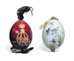 TWO RUSSIAN PORCELAIN EASTER EGGS PROBABLY BY THE IMPERIAL PORCELAIN FACTORY, LATE 19TH CENTURY EARLY 20TH CENTURY. One gilt to the front of the oxblood and purple glazed body with the cypher of Empress Alexandra Feodorovna beneath an Imperial crown, the other painted with cornflowers on a pale green ground.