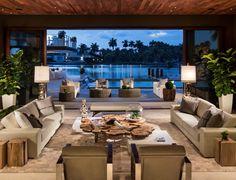 Sala de estar ampla com decoração natural, utilizando bastante madeira na composição. E a iluminação complementa o projeto com sua modernidade.