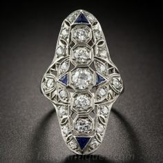 Just over 1 and 3/8 inches long, this dramatic Art Deco dazzler, dating from the 1920s-30s, features a central row of five bright white European-cut diamonds flashing from within hexagonal settings The central diamonds are joined by 18 additional diamonds and four triangular synthetic sapphires set at the cardinal points. A truly striking and stunning original Jazz Age jewel, expertly hand-fabricated in platinum. 1.70 carats total diamond weight. Currently ring size 6 1/2.