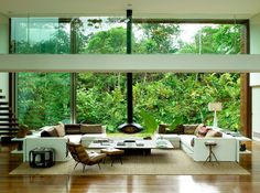 the wall of windows and the stunning tropical garden view in this modern living room are the show stoppers. The wall of lush green vegetation is stunning and captivating. The plants and trees create a living tableau...a beautiful backdrop for the entire room.