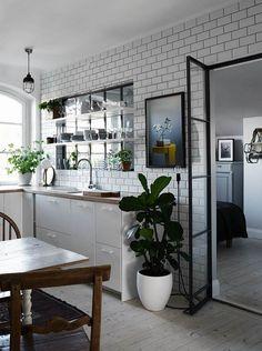 cuisine avec verrière intérieure, carrelage métro, sol en bois massif et meubles bas blanc laqué