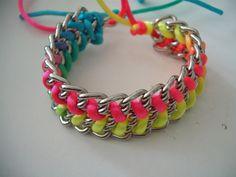 Ein breites Armband aus breiten Gliederketten mit eingeflochtenem Neon-Satinband.  Verschlossen wird das Armband durch einen Knoten im Satinband.