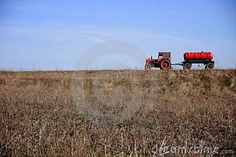 Photo about Red tractor with water tank on a field. Image of blue, wheel, tractor - 12410745
