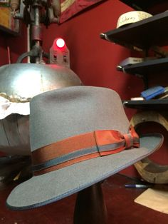 """A granite grey 100% beaver fur felt fedora. Two tone rust and grey ribbon, a top roan goat leather sweatband and sayin liner finish off this pinch front 2 1/8"""" brim fedora. Hand made in Milwaukee at The Brass Rooster with 100 year old equipment."""