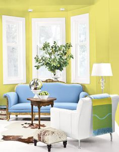 yellow green living room with antique blue couch and white armchair