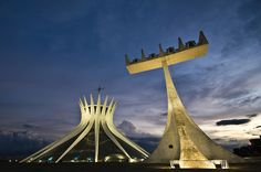 """The Cathedral of Brasília (Catedral Metropolitana Nossa Senhora Aparecida- """"Metropolitan Cathedral of Our Lady Aparecida"""" ) is the Roman Catholic cathedral serving Brasília, Brazil, and serves as the seat of the Archdiocese of Brasília. It was designed by Oscar Niemeyer, and was completed and dedicated on May 31, 1970. The cathedral is a hyperboloid structure constructed from 16 concrete columns, weighing 90 tons each.  A 20-meter (66 ft) tall bell tower stands outside the cathedral."""
