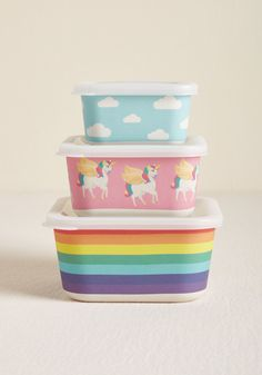 Nom and Collected Nesting Food Storage Set in Rainbow - You're totally chill knowing you've got all your day's nibbles stored stylishly in this set of three eco-conscious containers! Made from bamboo fiber, sealed with flexible plastic lids, and delightfully decorated with a rainbow, colorful unicorns, and a cloudy sky, this kid-friendly trio takes grubbing to the next level of gratifying.