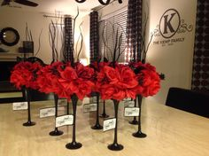DIY Black and red centerpieces. Can of spray paint, twigs, silk flowers and tea light stands.