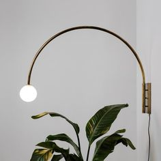 Break up rigid lines in your home with this curved wall lamp from Allied Maker. A large diameter hand bent arc effortlessly swivels against the wall, while a warm pleasant glow comes from a small glass sphere that is made by artisans in NYC. #wall #lighting