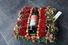 """Kleine wijnfles verwerkt in bloemstuk. Hier kan men het etiket personaliseren. Dit maakt het veel persoonlijker om te geven. Bv etiket met daarop """"proficiat met jullie 25ste huwelijksverjaardag"""""""