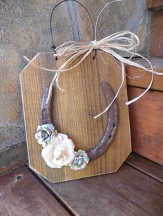 weather an old board, glue on a horse shoe and find decorative additives (maybe from scrap booking section? or jewelry from thrift store) tie with twine or jute