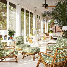 This screened porch is decked out with bambo lounge chairs with green and white patterned cushions. | Coastalliving.com