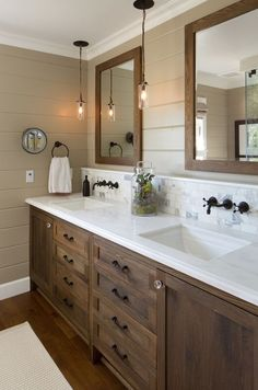 bathroom farmhouse with cabinets. Hanging pendant lights, feature wall, double mirror