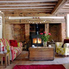 salon campagnard avec poutres en bois et heminée en briques