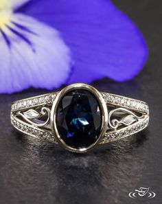 •Sapphire and Split Diamond Engagement Ring• Split shoulders graced with bead set diamonds hold a round blue sapphire. Filigree curls and leaves accent the rows of diamonds.