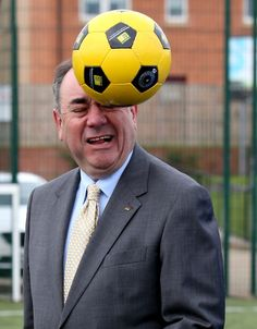 Scotland's First Minister Alex Salmond heads a ball during a Street Soccer Scotland photocall with Scotland under-21 midfielder Kenny McLean before the Scottish Cabinet meeting at Fernhill Community Centre in Rutherglen , the fifth in a series of meetings outside of Edinburgh following publication of Scotlandís Future in November last year. PRESS ASSOCIATION Photo. Picture date: Tuesday May 27, 2014. Photo credit should read: Andrew Milligan/PA Wire