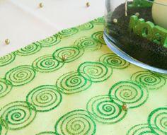 """La nappe ronde, de couleur ivoire, est habillée d'un chemin de table """"spirales""""."""