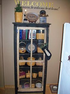 Longaberger basket display in cabinet with glass doors