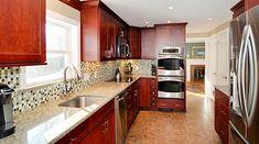 Norcraft Cabinetry in Maple Shaker Style Kitchen Cabinet,Glass Mosaic Backsplash, Stainless Steel Appliances, Quartz Stone countertop and Tiled Kitchen floor. #RhodeIslandKitchen www.cypressdesign...